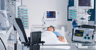 [photo] Man resting in hospital bed surrounded by man different machines
