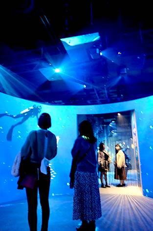 [foto] Dos mujeres en primer plano y dos en segundo plano mientras los proyectores en altura proyectan luz azul e imagen de un buzo en las paredes
