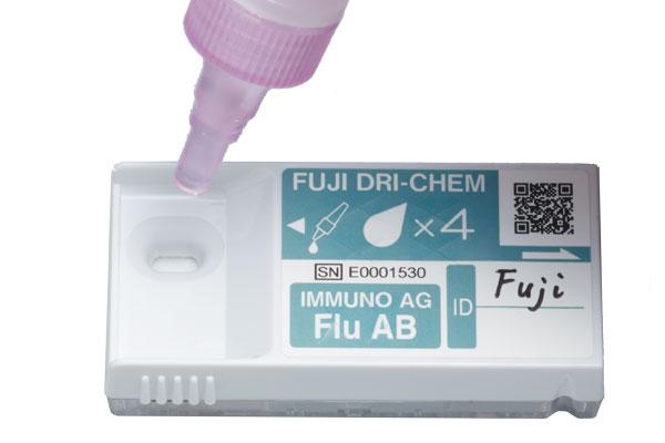 [photo] Dropper applying fluid to Fuji IMMUNO AG test cartridge
