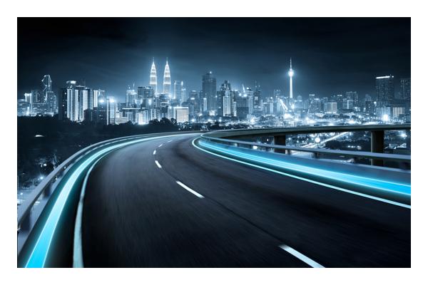 Calle iluminada por la noche con la ciudad a la distancia