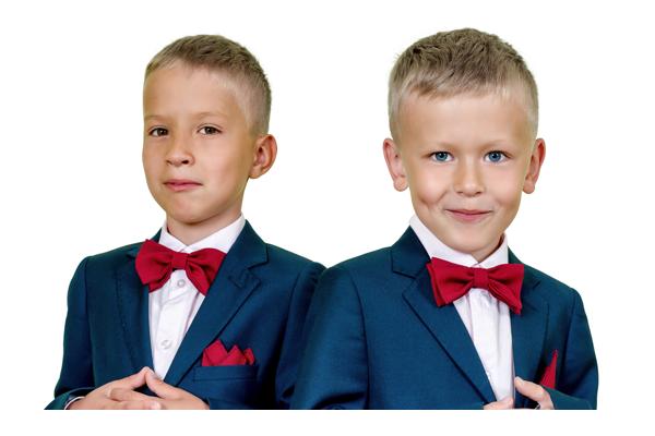 Dos niños con esmoquin y corbatas rojas