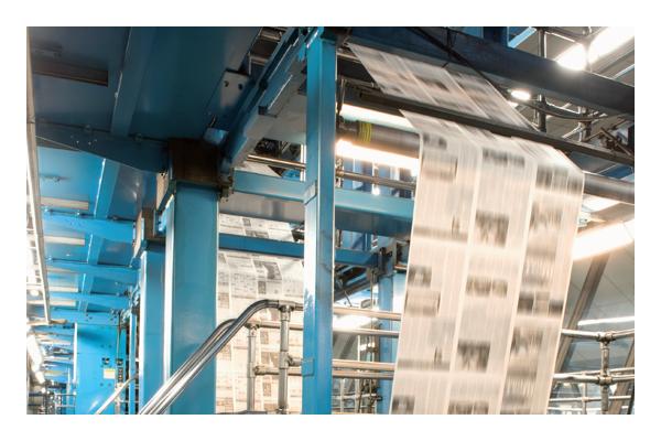 Newspaper flowing through printing machine