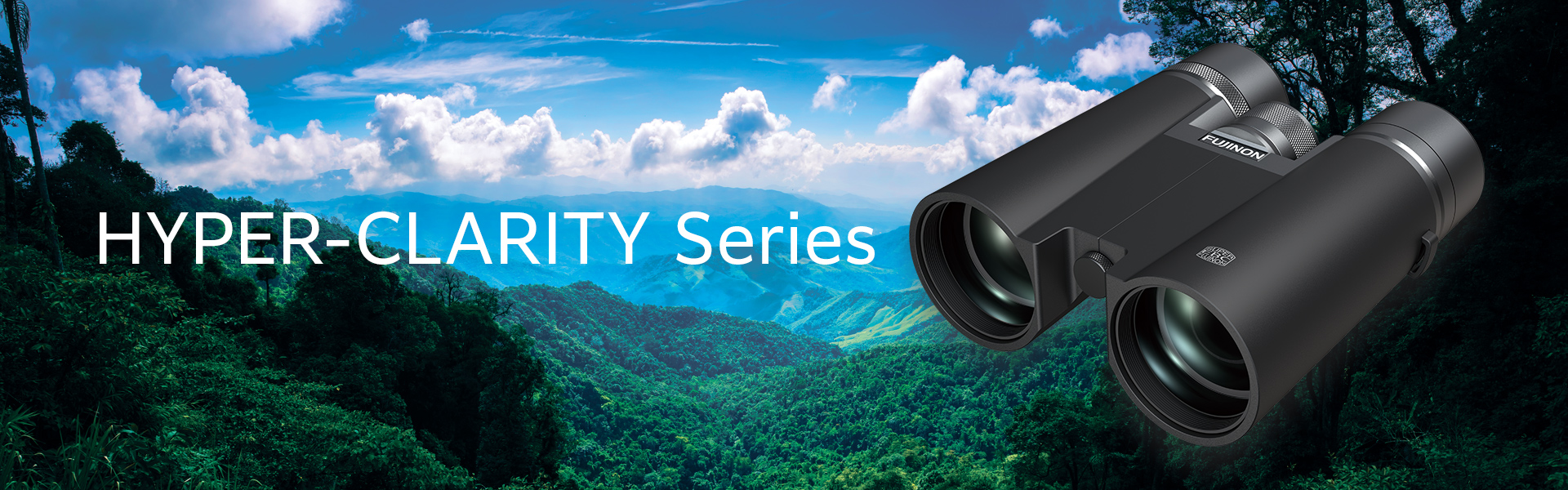 [image] Black Fuji Hyper-Clarity Series binoculars in front of green, mountainous hills and blue sky landscape background