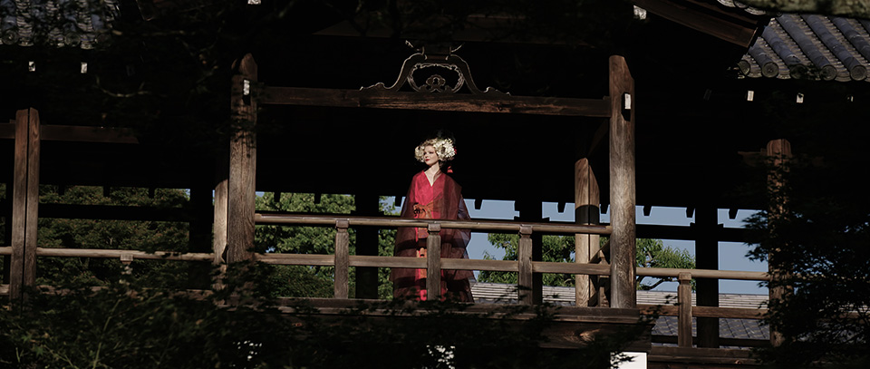 [photo] A more zoomed in wide shot of a lady in traditional Japanese attire standing under a tradional Japanese wooden house
