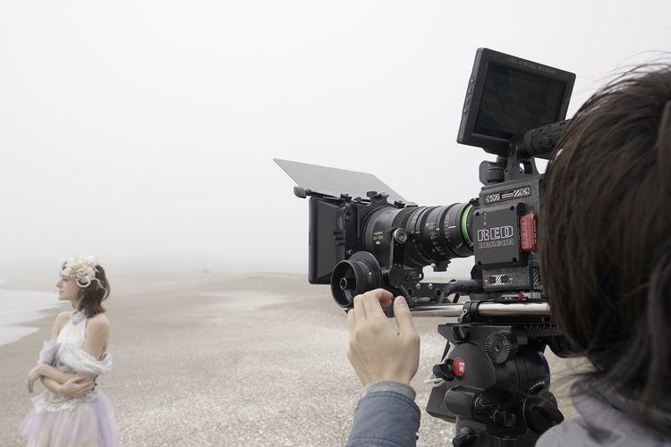 [photo] A cameraman filming a woman on the beach