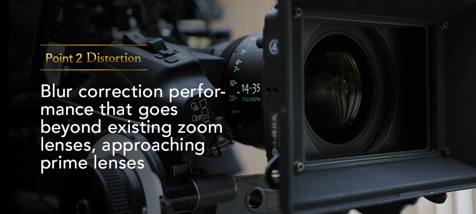 """[photo] """"Point 2 Distortion: Blur correction performance that goes beyond existing zoom lenses, approaching prime lens"""" text with a fully rigged digital camera as the background image"""