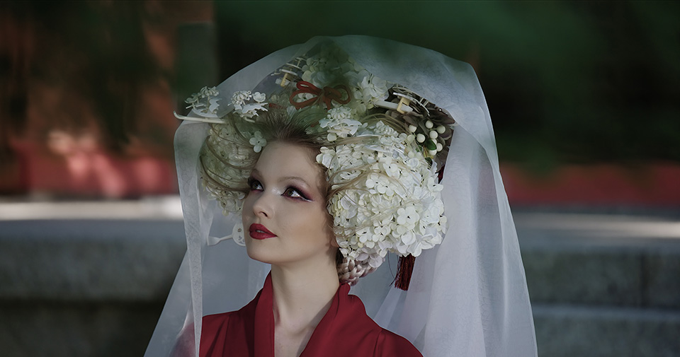 [photo] Close up of a lady in traditional Japanese attire and headgear with foreground leaves out of focus