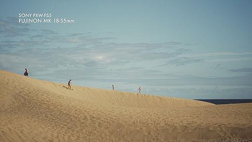 [photo] Landscape of people walking on beige sand dunes and blue sky overhead