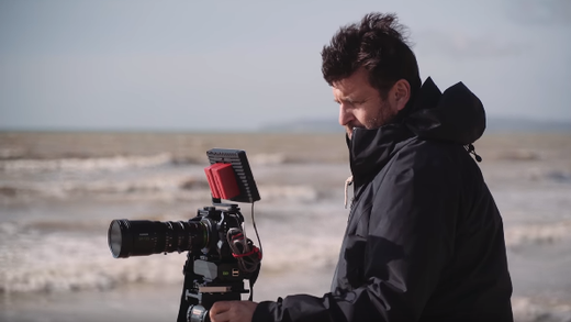 [photo] Man in black jacket at the beach filming on camera with MK series T2.9 lens