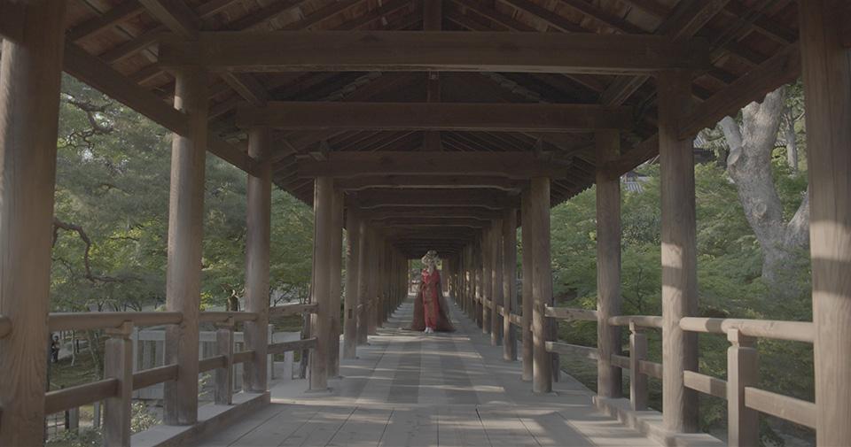 [사진] 일본 전통 의상을 입고 목조 다리 아래에 서 있는 여성의 모습을 채도를 낮추어 찍은 사진