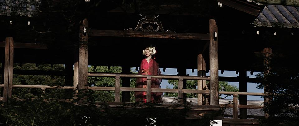 [사진] 전통 일본 의상을 입고 전통 일본식 목조 주택 아래에 서 있는 여성의 모습을 확대한 와이드 샷