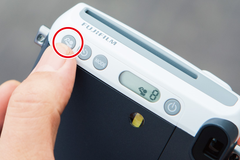 [photo] Highlighting the selfie mode button on the side of the Instax Mini 70 camera