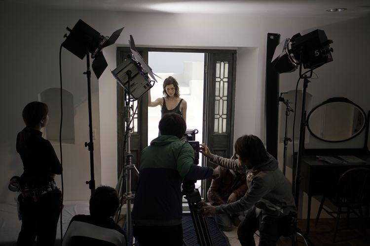 [사진] 열린 문에 서 있는 한 여성을 촬영하는 영화 촬영 기사