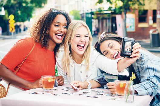[photo] 테이블에 앉아 있는 3명의 여자 친구들이 사진을 인쇄하는 동시에 인스탁스 미니 리플레이로 단체 사진을 촬영하는 모습