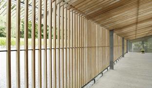 [사진] 후지논 14-35mm/F8 ZK 시리즈 렌즈를 사용하여 수평 및 수직선 왜곡을 강조하는 복도 위 나무 울타리와 지붕