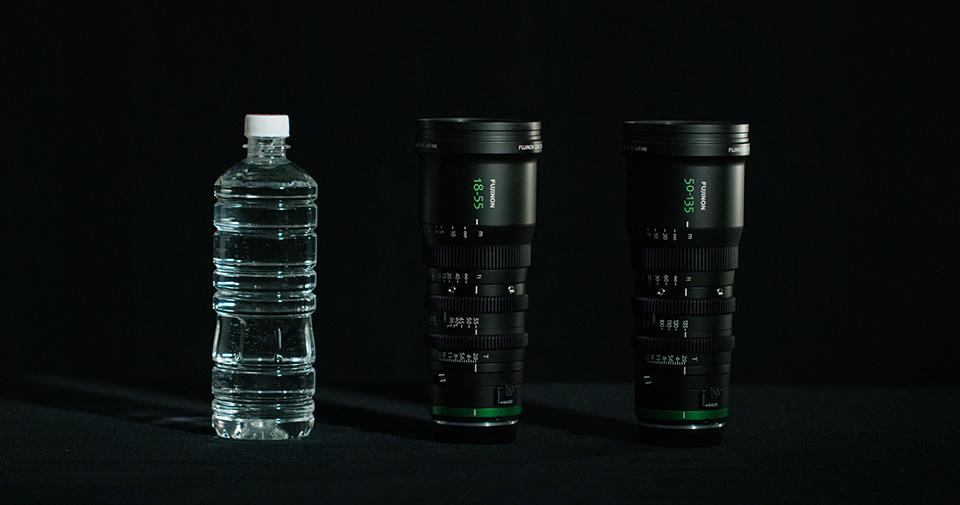 [사진] 블랙 배경의 MK 시리즈 렌즈와 그 옆에 놓인 물 병