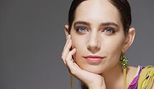 [사진] 후지논 58-300mm/F4 ZK 시리즈 렌즈를 사용하여 회색 벽 앞에 포즈를 취하는 여성 얼굴 클로즈업