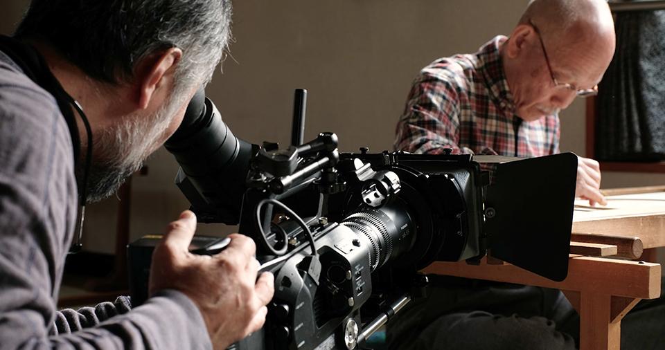 [사진] 뷰파인더를 통해 들여다보면서 자로 그림을 그리고 있는 피사체를 촬영하는 카메라맨