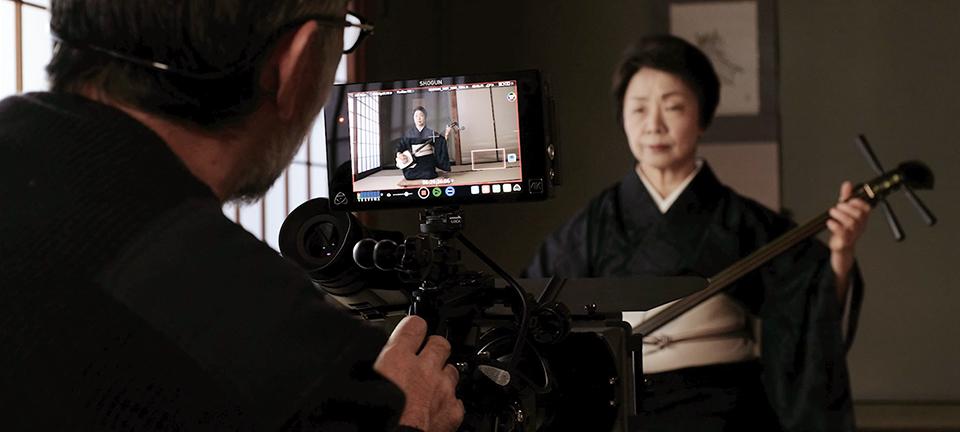 [사진] 외부 모니터를 보면서 일본의 기타 샤미센을 연주하는 한 일본 여성을 촬영하는 카메라맨