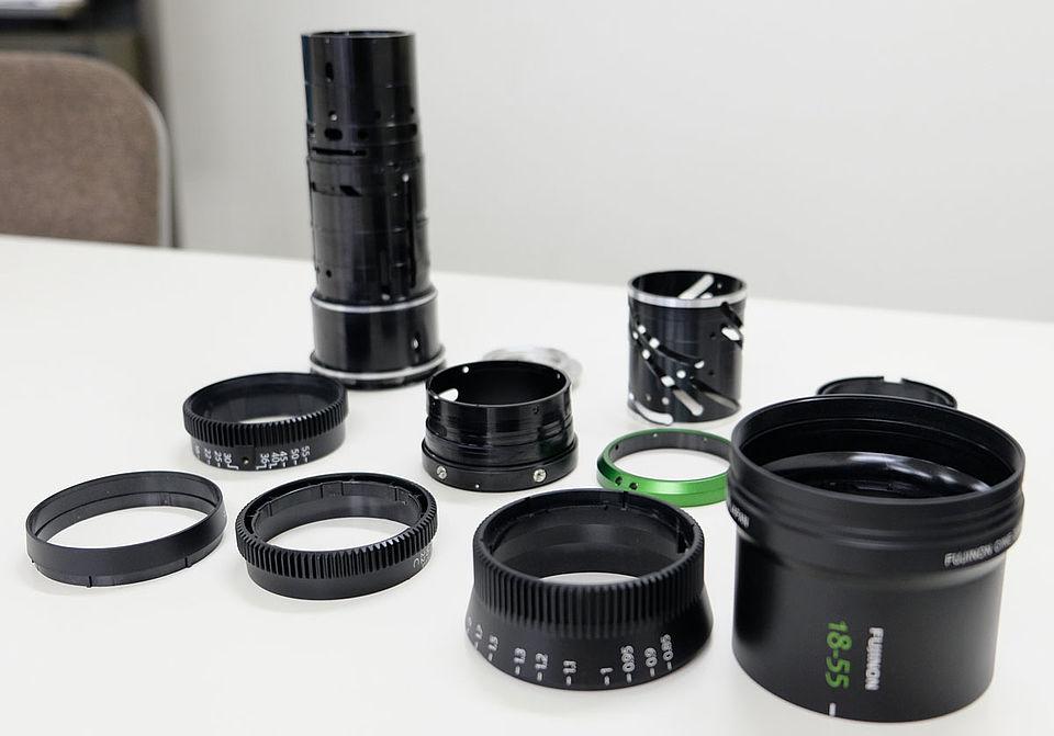 [사진] 테이블 위에서 포커스와 줌, 조리개 부품 등으로 후지논 18-55m 렌즈가 해체된 모습