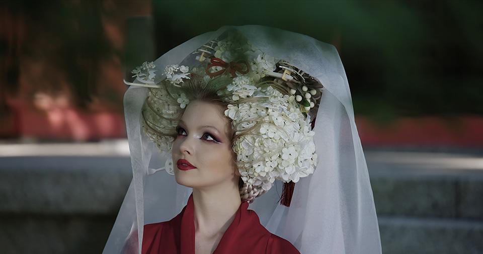 [사진] 일본 전통 의상과 모자를 착용한 여성의 근접 촬영 모습과 바로 앞에 초점에서 벗어난 나뭇잎 모습