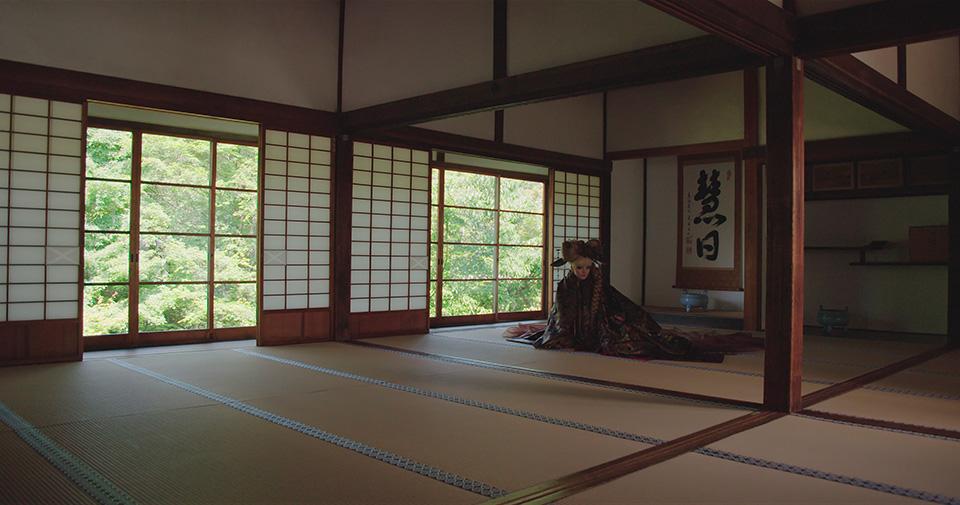 [사진] 일본 의상을 입고 일본 사원의 바닥에 앉아있는 여성의 모습을 채도를 높여 찍은 사진