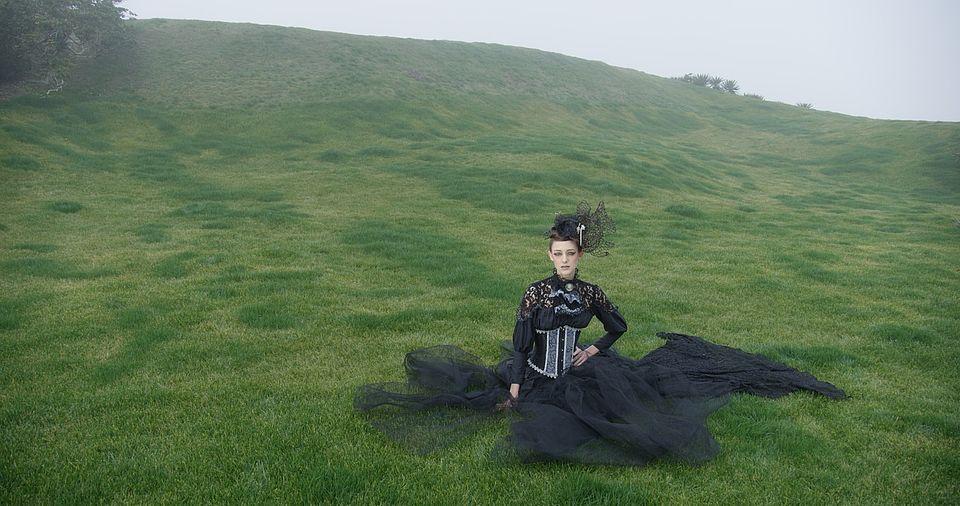 [사진] 흐린 날씨에 중세 의상을 입고 푸른 잔디 위에 앉아 있는 여성의 와이드 샷