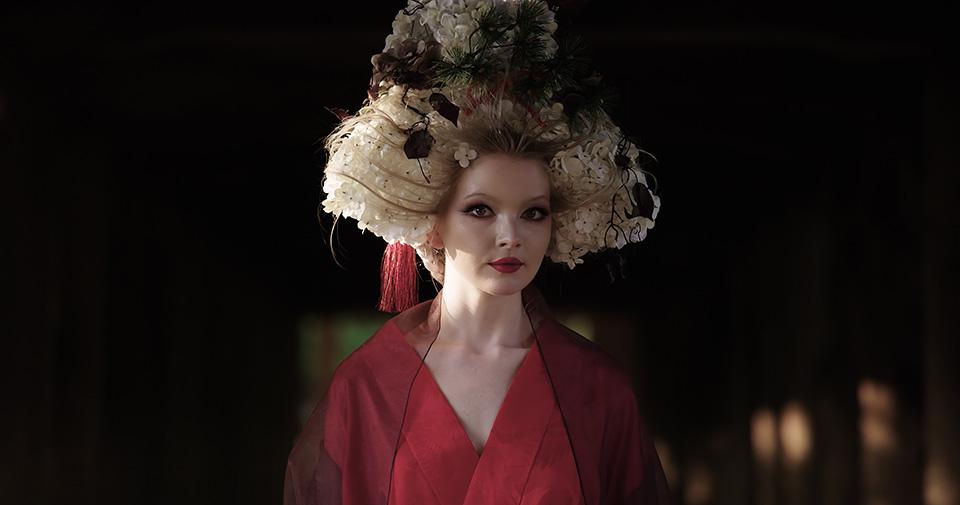 [사진] 일본 전통 모자와 복장을 착용하고 어두운 방에 서 있는 여성의 반신 모습