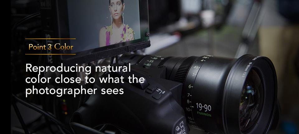 """[사진] """"포인트 3 색상: 사진 작가가 보는 것과 가까운 자연색 재현"""" 텍스트와 프레임 안의 여성 피사체를 보여주는 디지털 카메라 및 외부 디스플레이 모니터의 전면"""