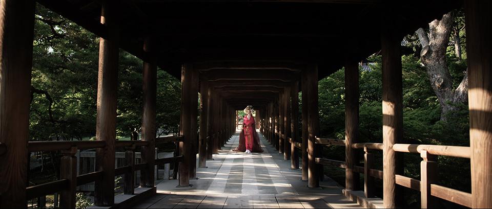 [사진] 일본 전통 의상을 입고 목조 다리 아래에 서 있는 여성의 모습을 채도를 높여 찍은 사진