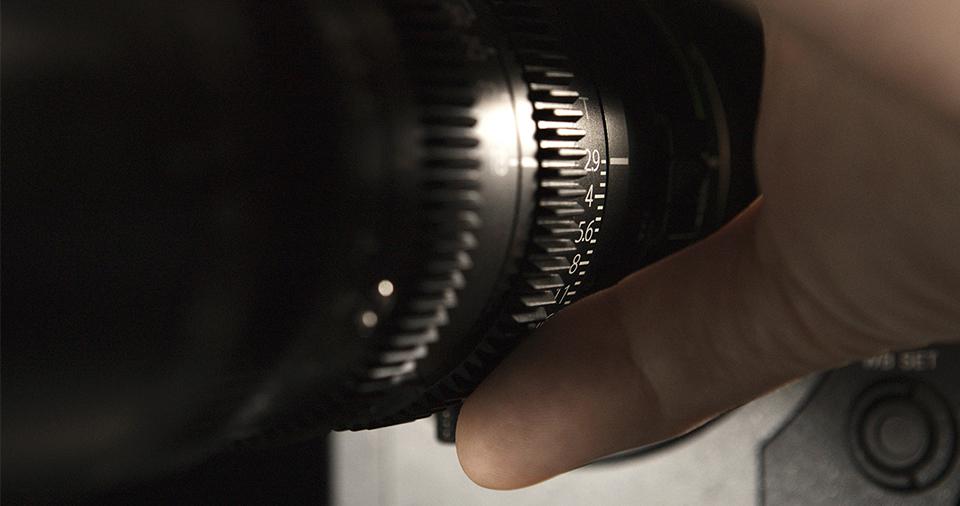 [사진] 카메라에 장착된 MK 렌즈의 조리개에 놓인 카메라맨의 손