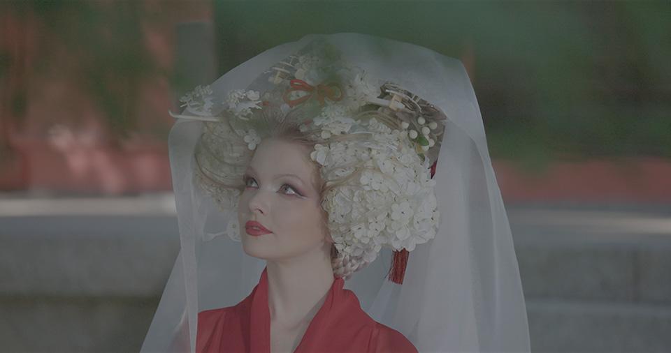 [사진] 일본 전통 헤드기어와 복장을 착용하고 위를 쳐다보는 여배우의 반신을 채도를 낮춰 촬영한 장면