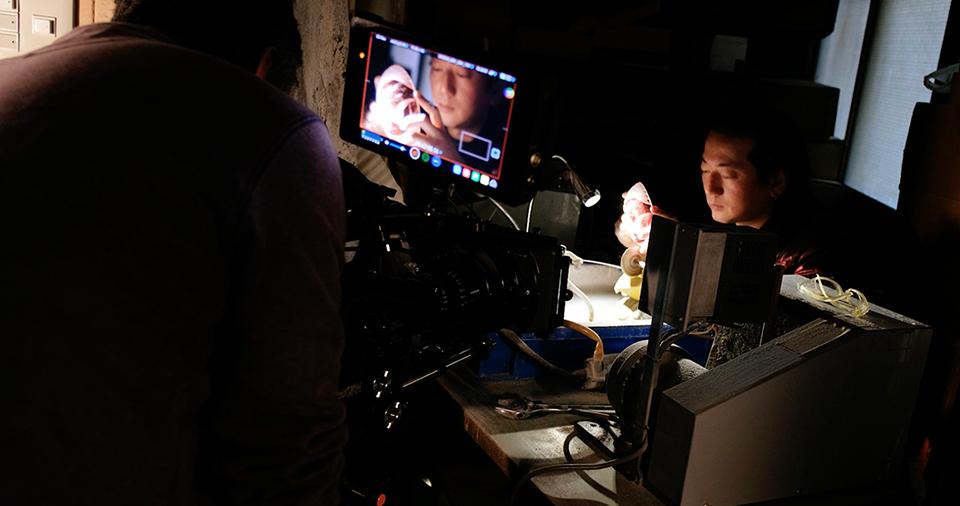 [사진] 램프 아래에서 작업하는 피사체를 촬영하는 카메라맨