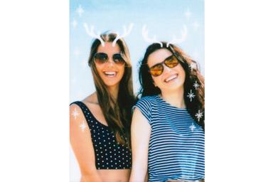 [photo] 카메라를 향해 미소 짓는 선글라스를 착용한 여자 친구 2명의 사진에 사슴뿔 프레임 적용