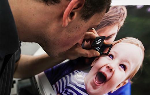 [photo] 사진 돋보기를 사용하여 아버지와 행복한 아기 사진의 품질을 검사하는 전문적인 남자
