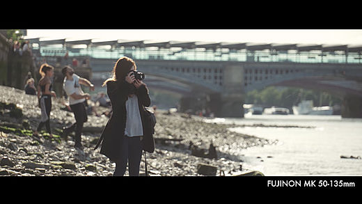 [photo] Woman standing on a beach in an open jacket, taking a photo with her camera