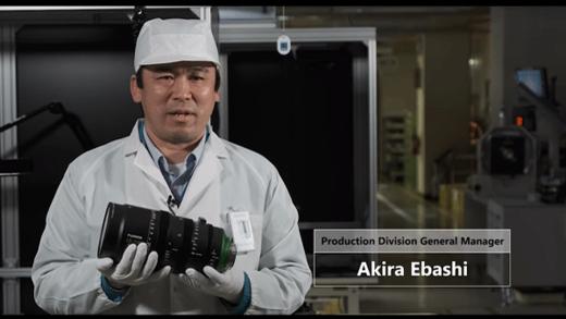 [사진] 흰색 실험실 가운을 입고 시네 렌즈를 들고 있는 후지필름 생산부장 아키라 에바시