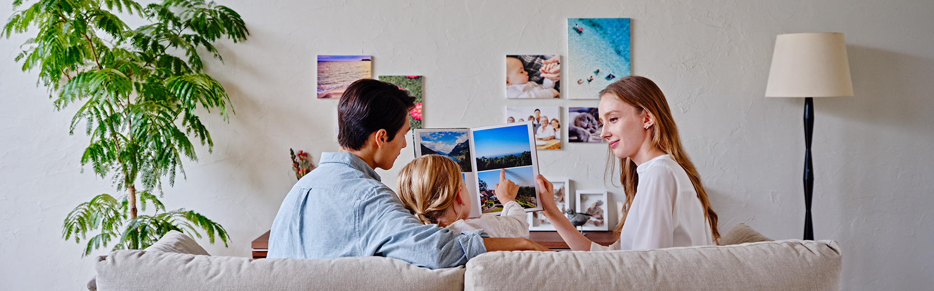 [photo] A young family of 3 sitting on a couch, looking through a photo album and facing a wall of family pictures