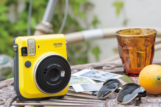 [photo] Instax Mini 70 in Canary Yellow sitting upright on a metal patio table
