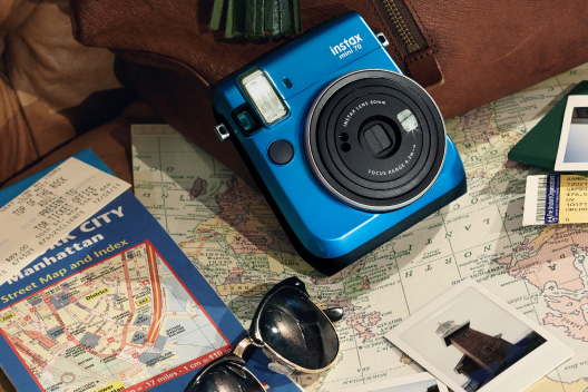 [photo] Instax Mini 70 in Island Blue laying on a bag and a map and travel decor