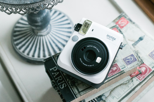 [photo] Instax Mini 70 in moon white on a stack of books