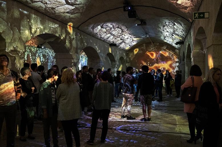 [사진] 대성당 스타일의 방 안에 모인 관람객들의 모습과 벽면, 바닥, 천장에 투사된 석재와 벽돌 이미지