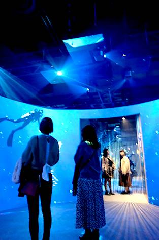 [사진] 오버헤드 프로젝터들이 벽면에 푸른 빛과 스쿠버 다이버의 이미지를 투사하는 동안 두 명의 여성은 전경에, 다른 두 명의 여성은 배경에 있는 모습