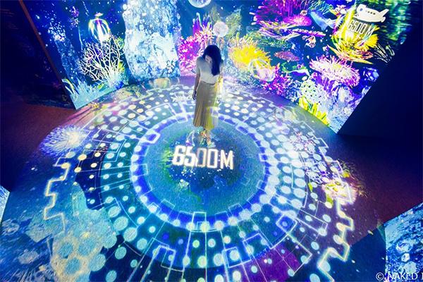 [사진]여러 가지 다채로운 빛이 사방에 가득한 방 중앙의 원 가운데 서 있는 여성