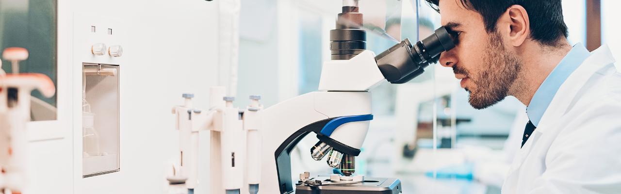 [image] 실험실에서 실험실 가운을 입고 현미경으로 관찰하는 남성