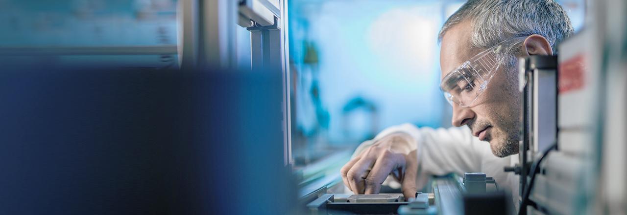 [photo] 안경을 쓰고 몸을 기울인 채 제조 기계를 면밀히 검사하고 있는 남성