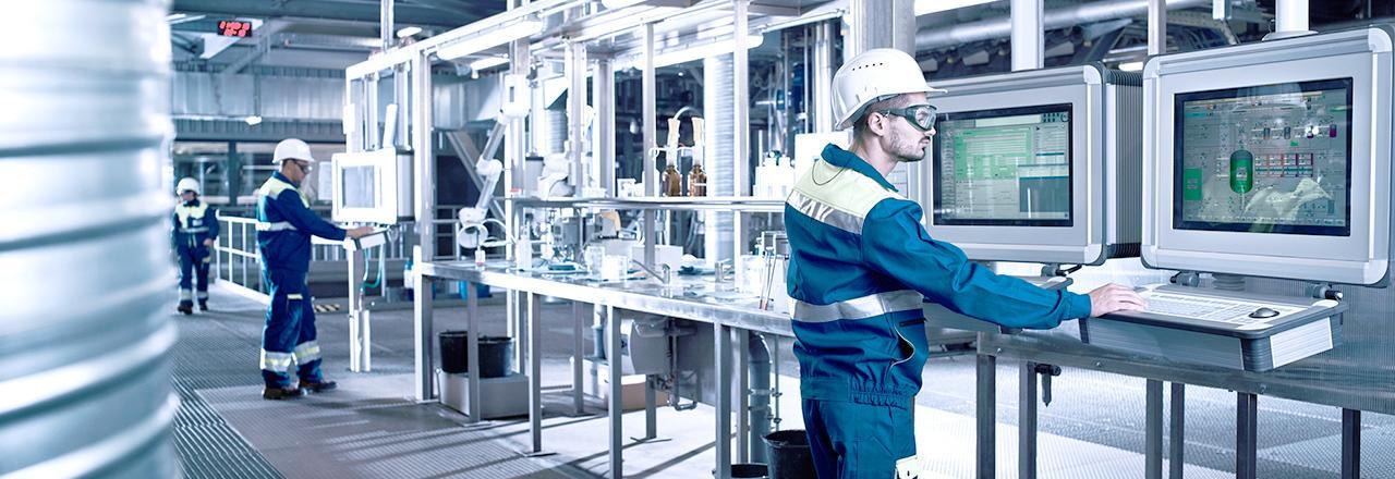 [사진] 안경, 안전모, 두꺼운 의복을 착용하고 제조 시설에서 두 대의 대형 컴퓨터 화면 앞에 서 있는 남성