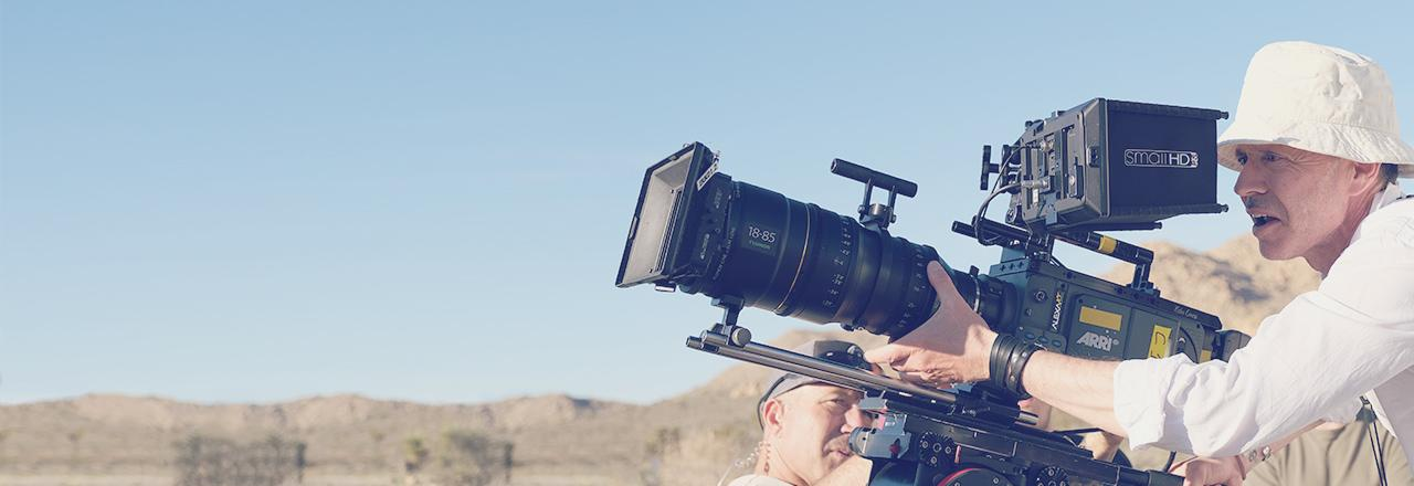 [photo] Man wearing white hat and shirt and filming in desert area with studio cameras using large Fujifilm lense