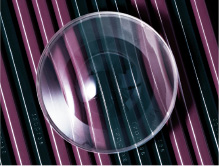 [photo] Clear, circular lens on top of black and purple striped surface