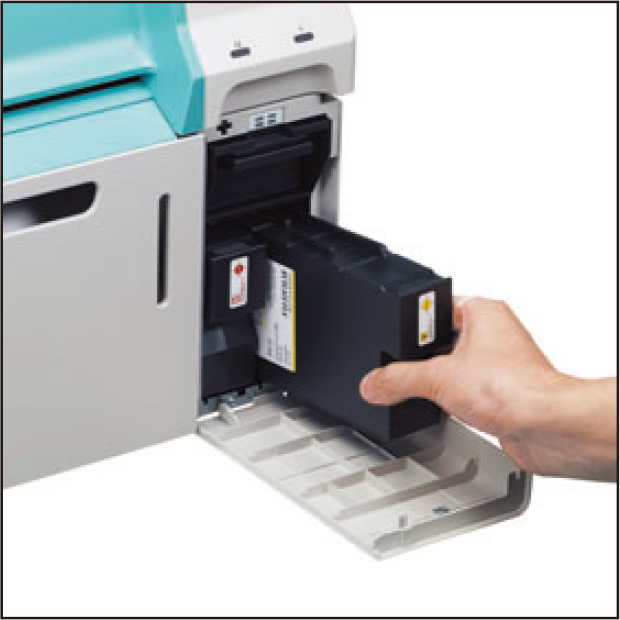 [photo] Hand putting ink cartridge replacement into ink slot of DE100 printer